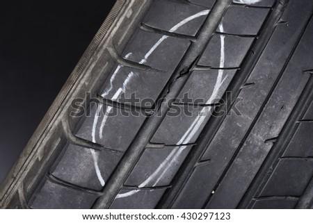 closeup of damaged car tire (studio shot) - stock photo