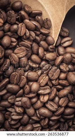 Closeup of dark roasted coffee beans on a rustic old wooden spoon used as a scoop. Food and drink backdrop showing aromatic and beautiful coffee beans.  - stock photo