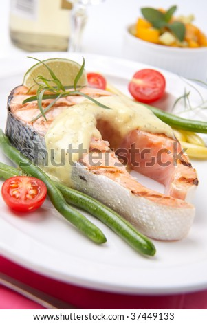 Closeup of delicious grilled salmon steak with tarragon sauce garnished with beans and cherry tomatoes. - stock photo