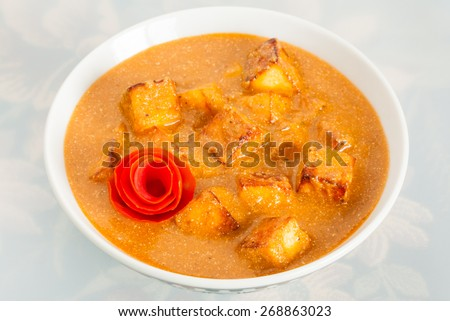 Closeup of delicious Indian paneer butter masala garnished with tomato peel. It is prepared using paneer (cottage cheese), butter, tomato and various spices. - stock photo