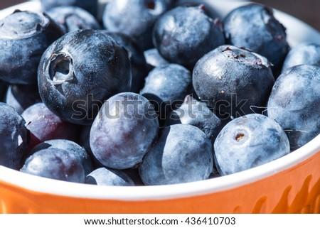 Closeup of delicious looking blueberries in an orange cup - stock photo