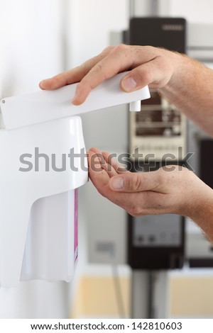 Closeup of dentist's hands using soap dispenser in clinic - stock photo
