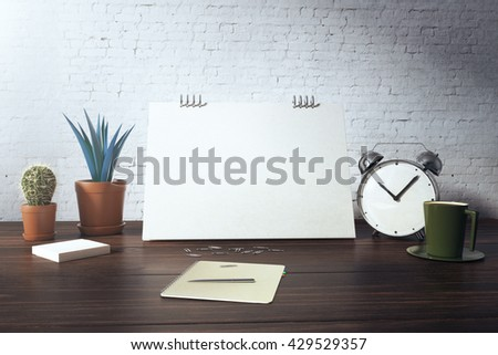 Closeup of desktop with blank card, plants, coffee cup, alarm clock and stationery items on white brick background. Mock up, 3D Rendering - stock photo