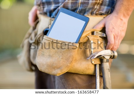 Closeup of digital tablet and hammer in carpenter's tool belt outdoors - stock photo