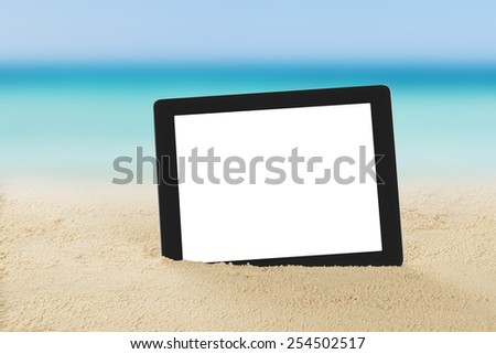 Closeup of digital tablet on sand at beach - stock photo