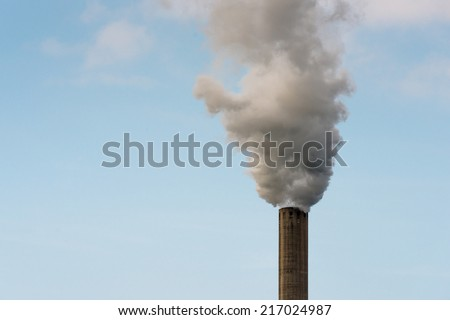 Closeup of dirty dark smoke clouds from a high industrial chimney against a clean blue sky - stock photo