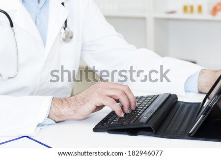 Closeup of doctors hands working on a Digital Tablet. - stock photo