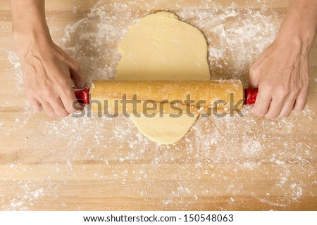 Closeup of dough being flattened on a wooden cutting board shot from above - stock photo