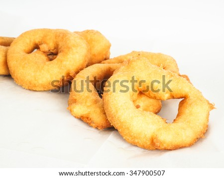 Closeup of doughnuts in pile on baking paper - stock photo