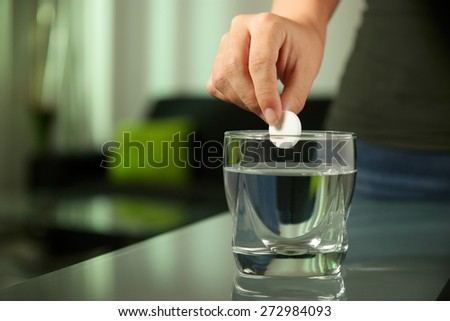 Closeup of effervescen tablet aspirin in glass of water, with sick young woman laying and relaxing on sofa in background - stock photo