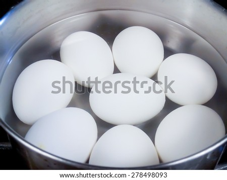 Closeup of eight whole hard-boiled white chicken eggs cooking in aluminum pot with hot water on stove - stock photo