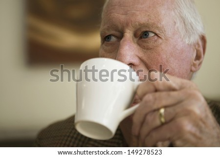 Closeup of elderly man drinking coffee while looking away - stock photo