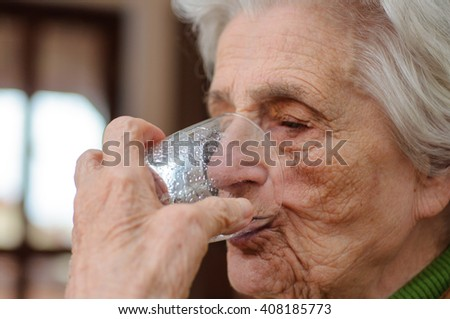Closeup of elderly woman drinking water from a glass - stock photo