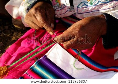 Closeup of elderly woman's hands spinning wool, Peru - stock photo
