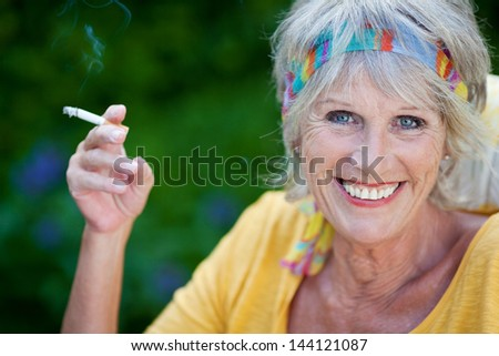 closeup of elderly woman smoking cigarette outdoors - stock photo