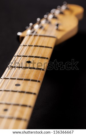 Closeup of electric guitar neck and head,focus on the fretboard - stock photo
