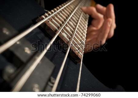 closeup of electrical bass guitar strings with fingers on it - stock photo