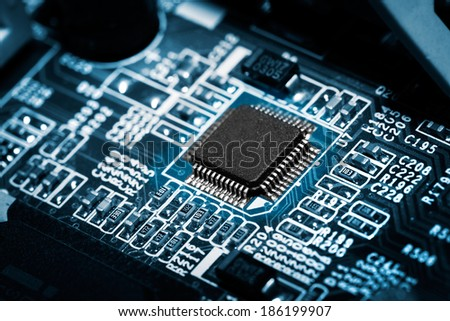 Closeup of electronic circuit board with processor on blue tone. - stock photo