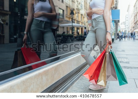 Closeup of elegant woman with shopping bags looking at boutique showcase in the city with copy space - stock photo