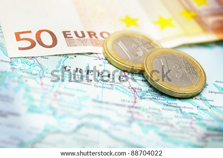 Closeup of Euro coins on a map of Greece - stock photo