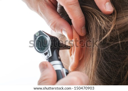 Closeup of examining ear with an otoscope - stock photo