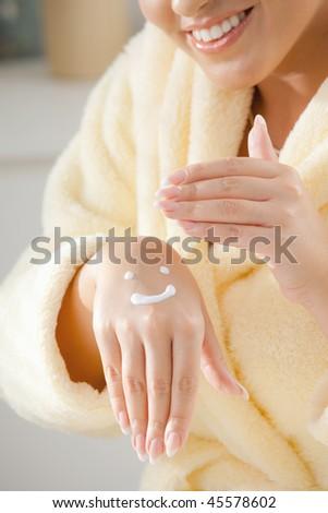Closeup of feemal hands applying hydrating cream. - stock photo