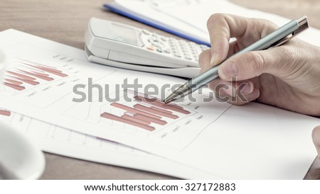 Closeup of female business accountant pointing to a graph with a pen as she works on tax report, with a retro filter effect. - stock photo