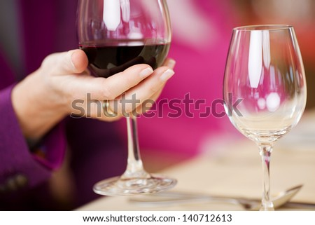 Closeup of female customer's hand holding wine glass at restaurant table - stock photo