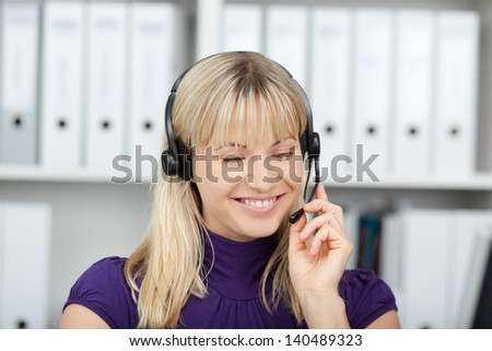 Closeup of female customer service executive using headset in office - stock photo