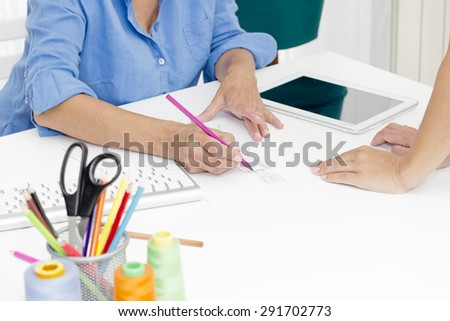 Closeup of female designers  having a meeting in a fashion design studio. - stock photo