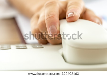 Closeup of female hand answering a call or hanging up holding handset of white landline telephone, shallow dof. - stock photo