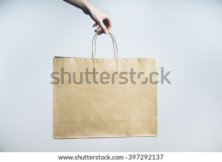 Closeup of female hand holding blank craft paper package, mock-up of empty brown shopping bag with handles - stock photo