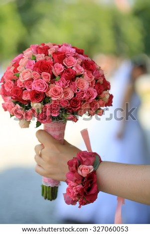Closeup of female hand holding one big beautiful colorful soft aroma fresh wedding bouquet of many pink and purple rose flowers sunny day outdoor on natural background, vertical picture - stock photo