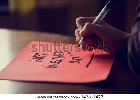 Closeup of female hand writing Happy Valentine's day phrase on red paper on wooden table, retro effect faded look. - stock photo