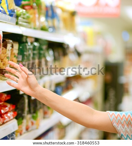 Closeup of female shopper picking products from shelves - stock photo