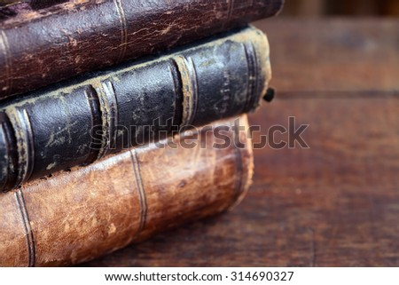 Closeup of few ancient books on old wooden table - stock photo