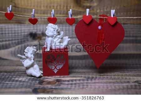Closeup of few beautiful cupid angels decorative figurine near red paper greeting valentine box and card on hanging ribbon on clothes-peg with no people on wooden background copy space, horizontal - stock photo