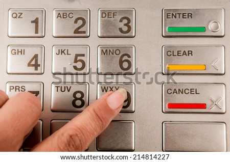 Closeup of finger pressing password in atm machine with metallic keyboard - stock photo