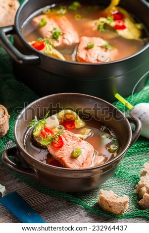 Closeup of fish soup spiced with dill and chilli pepper - stock photo
