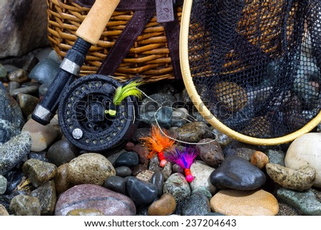 Closeup of fishing fly reel, landing net, creel and assorted flies on wet river bed stones  - stock photo