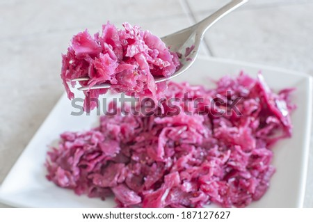 Closeup of fork full of fresh homemade sauerkraut with plate in background on tile counter - stock photo