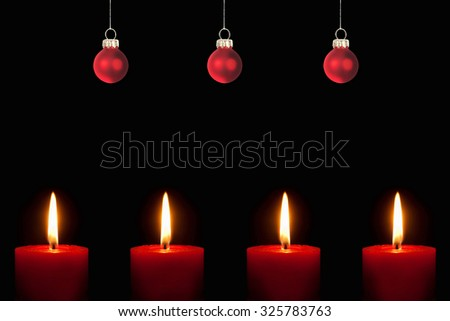 Closeup of four burning red candles and three christmas tree balls in front of black background - stock photo