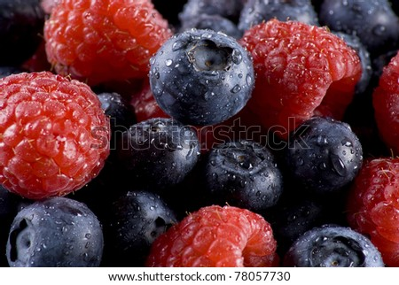 Closeup of fresh blueberries and raspberries mixed together - stock photo