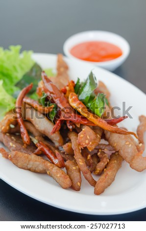 Closeup of fresh fried meat with sesame and chili - stock photo