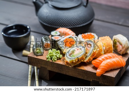 Closeup of fresh sushi on wooden board - stock photo