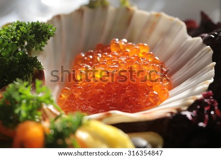Closeup of fresh useful delicious salty portion of red caviare served in sea queen white royal shell with green dill sunny day outdoor, horizontal picture - stock photo