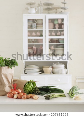 Closeup of fresh vegetables and paper bag on kitchen counter with utensils in cupboard - stock photo