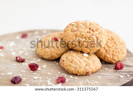 Closeup of freshly baked cranberry oatmeal cookies on wooden background - stock photo