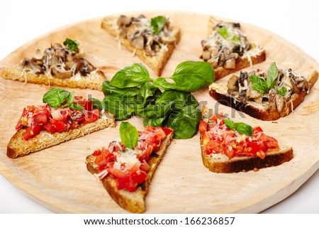 Closeup of freshly cooked tomato and mushroom bruschettas on a wooden board, isolated on white background - stock photo