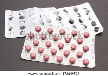 Closeup of full and empty pill blister isolated on black background - stock photo
